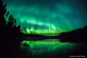 Groen noorderlicht reflecterend in een meer in centraal Finland. - Fotograaf: Johan van der Wielen