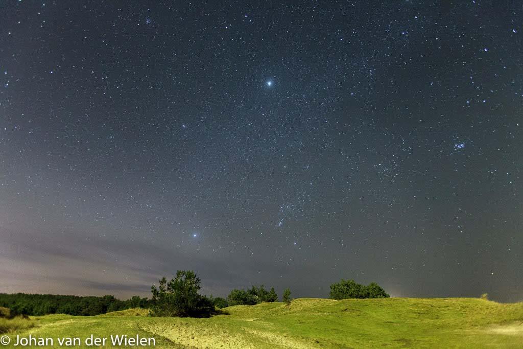 Nachtelijke hemel boven de duinen van Ameland met Orion, Jupiter en Venus.