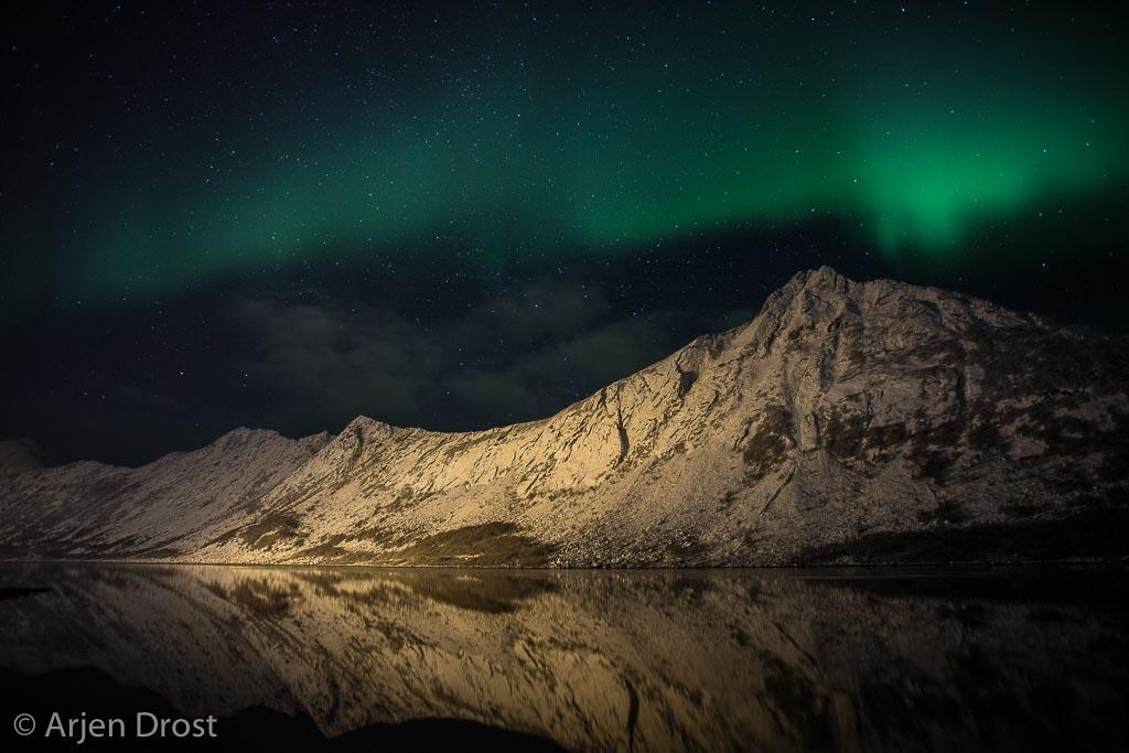 Noorderlicht boven de verlichte bergen van Gryllefjord